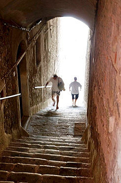 Italy, Linguria, Porto Venere, Men ascending stairs through an arched tunnel from seaside up to the main street.