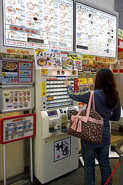 Woman purchasing meal tickets from a vending machine at a restaurant in Dotonbori, Osaka, Japan, Asia