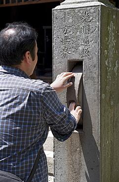 Man spinning a prayer wheel at Zenkoji Temple, Nagano City, Japan, Asia