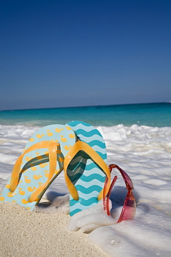 Two mismatched beach flip-flops with red sunglasses in the surf on a Caribbean beach, West Indies, Central America
