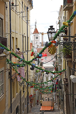 An alley is decorated with tinsel and colour for the annual Festival of St. Anthony in the Bica district of Lisbon, Portugal, Europe