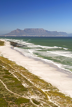 Aerial view along the coastline and beach of the Blaauwberg Nature Reserve on the west coast, north of Cape Town  with Table Mountain in distance across Table Bay, South Africa, Africa