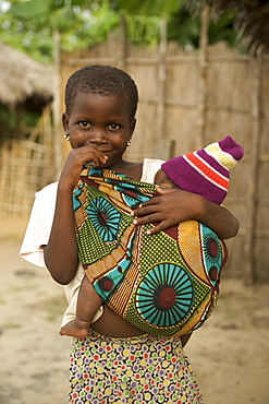 Child carrying baby in Guludo village in the Quirimbas National Park in northern Mozambique, Africa