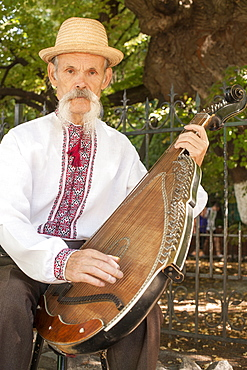 An elderly Ukrainian bandurist playing a bandura in a park in Kiev, Ukraine, Europe