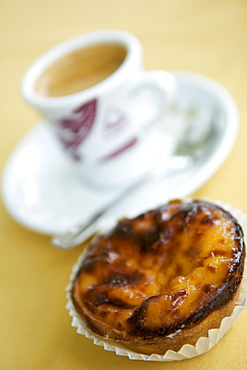 Cup of espresso and a pasteis de nata pastry in a Portuguese cafe.