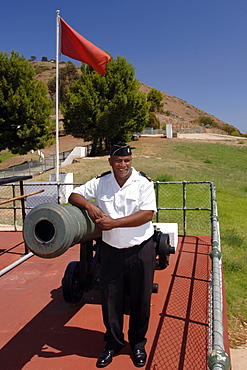 Chief Petty Officer Dudley Malgas of the South African Navy posing alongside the noon gun cannon in Cape Town. CPO Malgas has been in charge of firing the canon since 1995.  The daily noon gun is Cape Town's oldest living tradition and the two cannons used are the oldest guns in daily use in the world. They have marked the midday hour in the mother city in this distinctive, albeit noisy manner since early 1806. The cannons were cast in Britain in 1794 and still bear the royal crest of King George the third. The firing of the cannon was originally to give ships in the bay a means of re-setting their clocks accurately.
