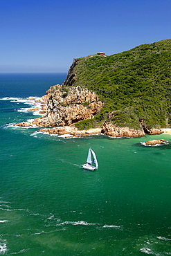 A catamaran sails through The Heads, the entrance to the Knysna lagoon on the Garden Route in South Africa.