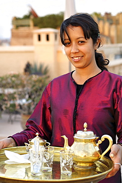 Moroccan girl serving tea on the rooftop of a riad in Marrakech, Morocco