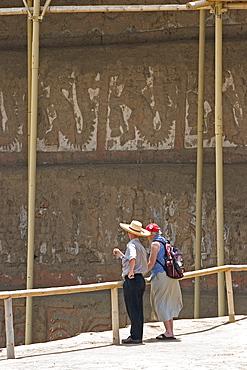 Guide with tourist at this adobe brick temple pyramid of the Moche people (100BC-AD850) in the desert north, Huaca de la Luna, Trujillo, Peru, South America