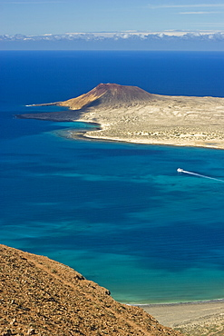 Volcanic cinder cone on Graciosa Island and the Graciosa to Lanzarote ferry in the Rio strait, seen from the Mirador del Rio on the north west coast of Lanzarote, Graciosa Island, Canary Islands, Spain, Atlantic, Europe