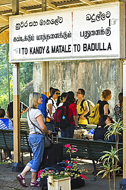 Foreign travellers await the popular Colombo to Badulla train at the railway station at Peradeniya, near Kandy, Sri Lanka, Asia