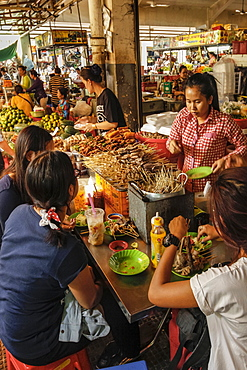 Young women eating sate at a stall in the eating area of this huge old market, Central Market, city centre, Phnom Penh, Cambodia, Indochina, Southeast Asia, Asia