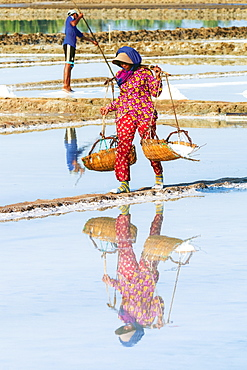 Woman with shoulder pole harvesting the salt fields around the Praek Tuek Chhu River estuary south of the city, Kampot, Cambodia, Indochina, Southeast Asia, Asia