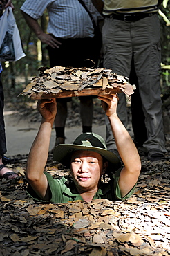 Vietnamese man descending into the tunnel system of the Vietcong in Cu Chi, South Vietnam, Vietnam, Southeast Asia, Asia