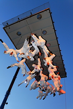 White-clad trapeze artists hanging upside down from a platform in the air, Global Rheingold, open-air theater by La Fura dels Baus, Duisburg-Ruhrort, Ruhrgebiet area, North Rhine-Westphalia, Germany, Europe