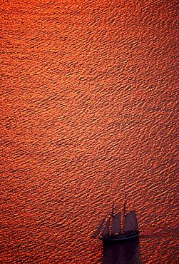 Sailing ship in the gleaming red Mediterranean Sea off the island of Santorini, Cyclades, Greece, Europe