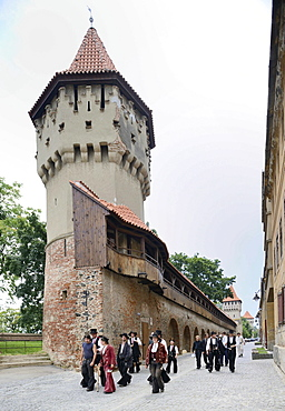 Travelling journeymen standing in front of defensive wall and tower of the craft guilds in Strada Cetatii, Sibiu, Romania, Europe