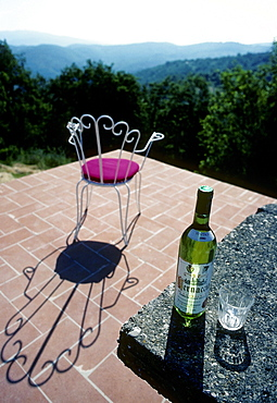 Solitary chair on a terrace overlooking the Chianti region, fantastic views, bottle of white wine and a glass on a table, holiday atmosphere, Sienna, Tuscany, Italy, Europe