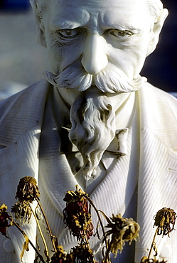 Sad old man with a moustache and a goatee beard with dried flowers, sculpture on a grave, historic cemetery of Nice, France, Europe