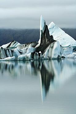 Floating icebergs, coloured with black lava ash, in the Joekulsarlon glacier lagoon of the Vatnajoekull Glacier, Iceland, Europe