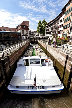 Tourist boat travelling through a lock on the Ill River, Petite France, Strasbourg, Alsace, France, Europe