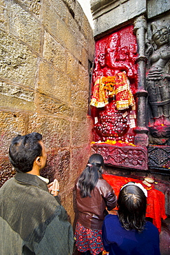 Pilgrims in front of a red-coloured stone statue in Kamakhya Temple, a Hindu temple, Guwahati, Assam, North East India, India, Asia