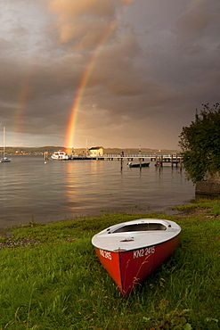 Red boat on Lake Constance in front of a pier with a rainbow on the horizon, Baden-Wuerttemberg, Germany, Europe