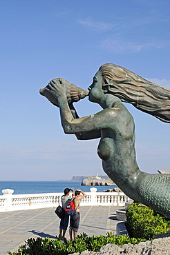 Tourists standing next to the sculpture of a mermaid blowing a chonch shell, La Magdalena peninsula, Santander, Cantabria, Spain, Europe