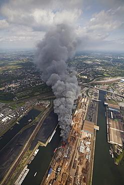 Aerial view, smoke, fire on a scrap island in the Duisport inland port, Duisburg, Ruhrgebiet region, North Rhine-Westphalia, Germany, Europe