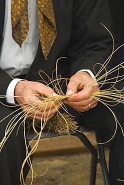 Hands of a man preparing esparto to make baskets at the Santa Eulalia yearly traditional handicrafts fair, Santa Eulalia, Ibiza, Spain, Europe