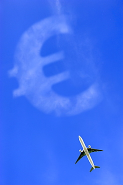Aircraft flying against a blue sky with a Euro sign, symbolic image for aviation tax