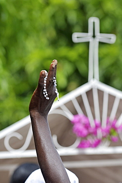 Raised hand with rosary in front of a cross, parish of Sacre Coeur, Turgeau district, Port-au-Prince, Haiti, Caribbean, Central America