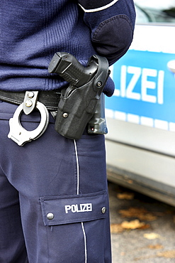 Police, police car, police officer with handcuffs and service weapon, Walther P99, in the holster