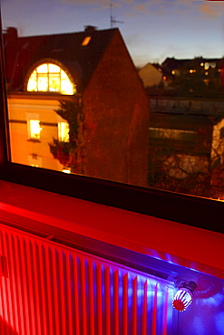 Radiator at a window with an illuminated thermostat, heating costs