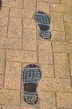 Thomas Tredyngton's footprints in the pavement by Catchcold Tower, medieval city walls, city centre, Southampton, Hampshire, England, United Kingdom, Europe