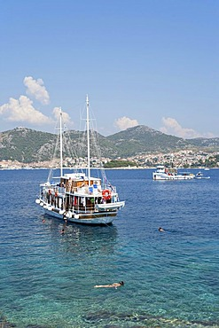 Excursion boats anchoring off Stipanska Island, Hvar Island at back, Central Dalmatia, Adriatic Coast, Croatia, Europe