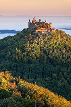 Hohenzollern Castle in the morning light with autumn forests, early morning fog, Swabian Alb, Baden-Wuerttemberg, Germany, Europe