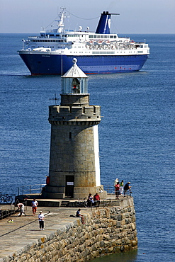 Cruise ship anchoring off the pier with lighthouse at Castle Cornet, port fortress, entrance to the port of St. Peter Port, Guernsey, Channel Islands, Europe
