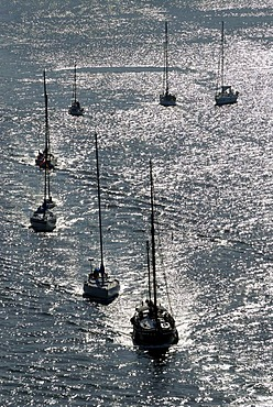 Sailing boats and motorboats in back light