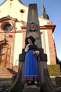 Second World War memorial with statue of woman wearing traditional Alsatian costume in front of a church, Ingersheim, Alsace, France, Europe