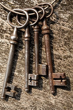 Old barn door keys on a wooden board