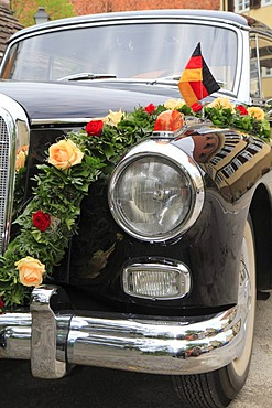 Vintage Mercedes Benz 300 car with wedding decorations and German flag