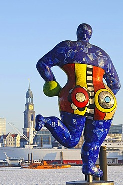 Nana sculpture in front of the tent of the musical The Lion King in the Hamburg harbor, rear view, in the back the St. Michaelis church, Landungsbruecken jetties, Hamburg, Germany, Europe
