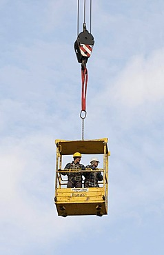 Workers standing inside the raised safety cage of a building crane, industrial safety, construction industry