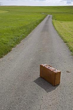 Suitcase, country road, symbolic image Last trip, death