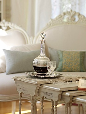 Fine wine carafe with glass on white-painted table, with a stylish sofa