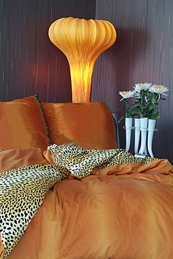 Luxurious bed in an exclusive design with a stylish lamp