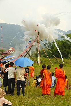 Festival, rocket firing, bang fai, launch and explosion of a rocket on the launch pad, monks in orange robes looking on, Muang Xai, Oudomxay province, Laos, Southeast Asia, Asia