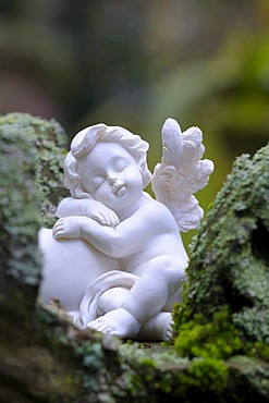 Angel figurine made of clay on mossy stones