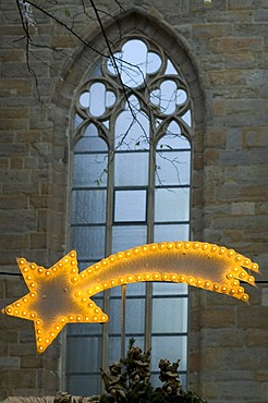 Illuminated Christmas star in front of a stained glass window